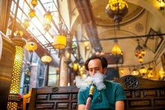Man som röker den turkiska vattenpipan Arkivfoto