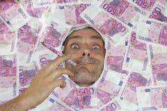 Man som röker euroanmärkningen Arkivfoto