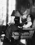Man som röker i vardagsrum (alla visade personer inte är längre uppehälle, och inget gods finns Leverantörgarantier att det ska g Arkivfoto