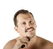 Man som rakar framsidan med rakapparaten Arkivfoto