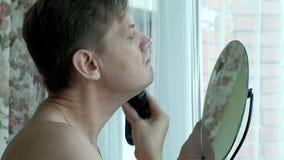 Man som rakar skägget med den elektriska rakapparaten Kontrollera att raka nalla ditt finger på kinden closeup Royaltyfria Foton