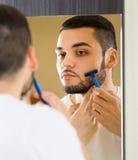 Man som rakar skägget med en rakkniv Arkivbilder