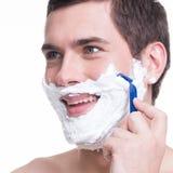 man som rakar skägget med rakkniven Arkivbild