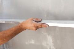 Man som rappar en vägg genom att använda sväva regel för att kontrollera plattheten Royaltyfri Foto