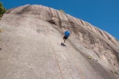 Man som Rappelling från klippan Arkivbild