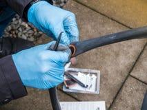 Man som reparerar cykeln med det plana gummihjulet Arkivfoto