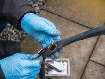 Man som reparerar cykeln med det plana gummihjulet Royaltyfri Foto