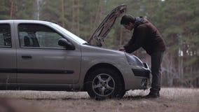 man som reparerar den brutna bilen