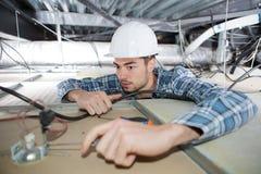 Man som reparerar elektriskt ledningsnät på tak Royaltyfri Bild