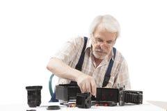 Man som reparerar en gammal kamera Arkivfoto