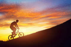 Man som rider en bmxcykel som är stigande mot solnedgånghimmel Styrka utmaning Arkivbild