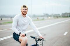 Man som rider en cykel på en väg Royaltyfri Bild