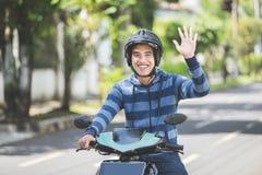 Man som rider en moped och vinkar handen arkivfoto