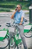 Man som rider en stadscykel i formell stil arkivbild
