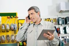 Man som rymmer den Digital minnestavlan, medan genom att använda mobilephonen fotografering för bildbyråer