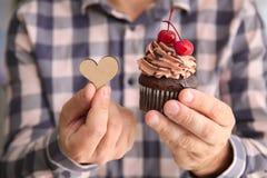 Man som rymmer den smakliga muffin och trähjärta fotografering för bildbyråer