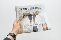 Man som rymmer den Wall Street Journal tidningen med Emmanuel Macr Arkivfoto