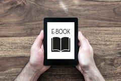 Man som rymmer eBookavläsaren på den lantliga trätabellen royaltyfri foto