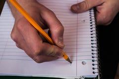 Man som rymmer en anteckningsbok och en blyertspenna arkivbilder
