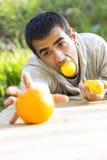 Man som rymmer en apelsin arkivfoton