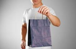 Man som rymmer en blå gåvapåse close upp Isolerad bakgrund royaltyfri bild
