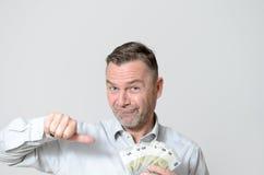 Man som rymmer en fan av fem euroanmärkningar Royaltyfria Bilder