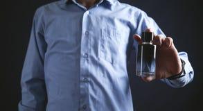 Man som rymmer en flaska av doft arkivfoton