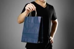 Man som rymmer en gåvapåse close upp Isolerat på grå bakgrund arkivbild