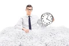 Man som rymmer en klocka i en hög av strimlat papper Fotografering för Bildbyråer