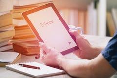 Man som rymmer en modern ebookavläsare Arkivfoto