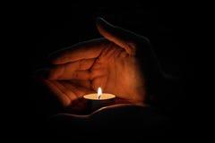 Man som rymmer en stearinljus i mörkret Arkivfoto