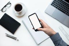 Man som rymmer en telefon med den isolerade skärmen över skrivbordet i kontoret royaltyfria foton