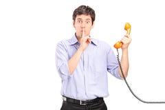 Man som rymmer en telefon och göra en gest tystnad Arkivfoto