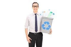 Man som rymmer ett återanvändningsfack fullt av plast- flaskor Royaltyfri Bild