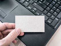 Man som rymmer ett tomt pappaffärskort och använder bärbara datorn Royaltyfri Bild