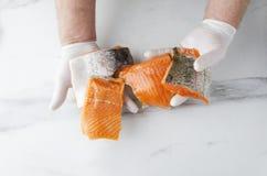 Man som rymmer flera stycken av den nya rå laxen Smakliga stycken av fisken royaltyfria foton