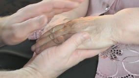 Man som rymmer gamla rynkiga händer av den äldre kvinnan arkivfilmer