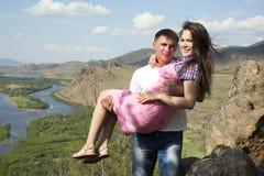 Man som rymmer hans flickvän i hans armar Arkivbild