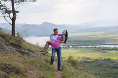 Man som rymmer hans flickvän i hans armar Fotografering för Bildbyråer