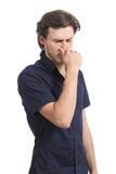 Man som rymmer hans näsa som luktar stank Fotografering för Bildbyråer
