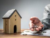Man som rymmer tangenten med modellhuset Sparande pengarbegrepp, fastighet- och egenskapsbegrepp, hushållbesparingar och finanser royaltyfria bilder