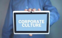 Man som rymmer text för företags kultur i minnestavlaskärm arkivfoton