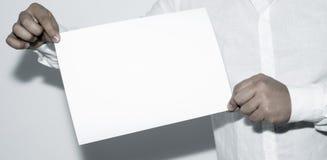 Man som rymmer tomt papper på vit bakgrund royaltyfri bild
