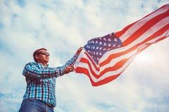 Man som rymmer USA flaggan Fira självständighetsdagen av Amerika Juli 4th Royaltyfri Bild