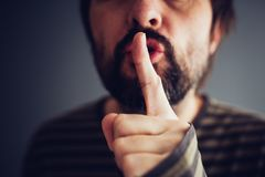 Man som säger att hyssja eller vara tyst arkivbild
