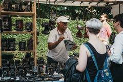 Man som säljer filmkameror på ett stånd på Portobello vägmor arkivfoto
