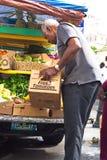 Man som säljer jordbruksprodukter arkivbild