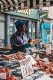 Man som säljer ny frukt i tegelstengränden, London, UK royaltyfria bilder