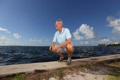 Man som sätta sig på skyddsmuren mot havet Arkivbilder
