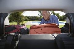 Man som sätter bagage in i bilkängan Fotografering för Bildbyråer